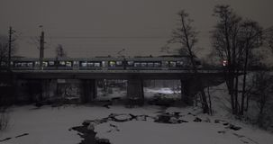 Evening view of passenger train running across the bridge in winter city stock footage