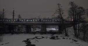 Evening view of passenger train running across the bridge in winter city. Modern commuter train crossing the bridge in the city. Scene in late winter evening stock footage