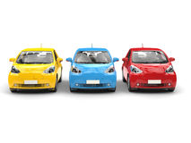Modern compact urban electric cars in primary colors - front view Royalty Free Stock Photos