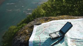 Modern compass with paper terrain map on the weathered stone near wide mountain stream stock footage
