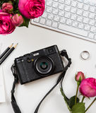 Modern computer keyboard, pink flowers and photo camera on white Royalty Free Stock Photography