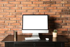 Modern computer monitor on desk brick wall, mock up with space for text. Modern computer monitor on desk against brick wall, mock up with space for text royalty free stock photography