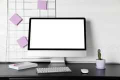 Modern Computer Monitor On Desk Against Light Wall, Royalty Free Stock Photo