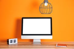 Modern computer monitor on table against color wall Stock Photo