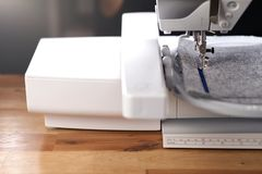 modern computerised sewing machine with embroidery unit in bright light stitching a blue frame on grey felt stock photos