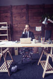 Modern concept of freelance work of young man. Toned image of young modern freelancer sitting at wooden desk, talking on phone Stock Photography