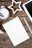 Modern conceptual wooden office or home desk table with tablet, note book, cup of pens, wooden star, businesscard and table clock Stock Photos