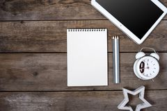 Modern conceptual wooden office or home desk table with tablet, note book, cup of pens, wooden star, businesscard and table clock. Stock Photography