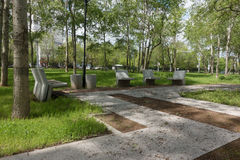Modern concrete benches and path in a public park. Modern concrete benches and path in a public park with green grass and trees on a beautiful spring day royalty free stock image