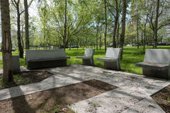 Modern concrete benches and path in a public park. Modern concrete benches and path in a public park with green grass and trees on a beautiful spring day royalty free stock photos