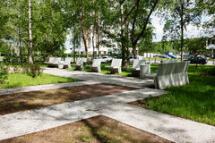Modern concrete benches and path in a public park. Modern concrete benches and path in a public park with green grass and trees on a beautiful spring day stock image