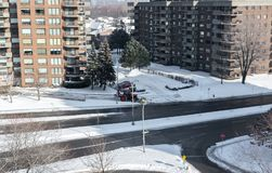 Modern condo buildings with huge windows and balconies and the snow removal tractor in Montreal Royalty Free Stock Photos