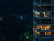 Modern condo by night. View of a modern condo by night with lights on in some apartments Stock Image