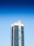 Modern Condo Tower with Balconies Under Blue Skies. A solo modern condo tower with balconies under a clear blue sky Stock Images