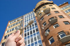Modern Condominium. On a background of a modern brick house, hand with keys from an apartment Stock Image