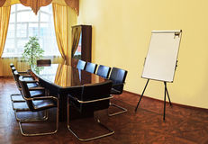 Modern conference room. Modern interior of empty conference room with window, flipchart and wooden table Stock Images
