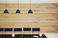 Modern conference room with lamps, furniture and wooden wall Royalty Free Stock Image