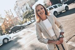 Modern and confident. Beautiful young woman in suit looking away and smiling while standing outdoors stock images
