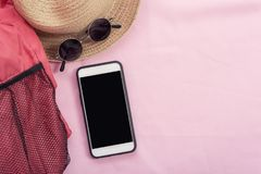 Modern connection technology background, mobile, red bag, hat an. D sunglasses on pink background. Lifestyle travel background Royalty Free Stock Photo