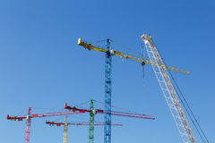 Modern construction cranes in front of blue sky. Modern construction cranes in front of blue sky royalty free stock images