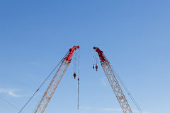 Modern construction cranes in front of blue sky. Modern construction cranes in front of blue sky royalty free stock image