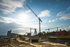 Modern construction site. Scenic view of cranes on modern construction site with blue sky and cloudscape background Royalty Free Stock Photos
