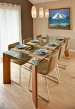 Modern / Contemporary Dining Room. Contemporary dining room, mid-century modern styling.  Glass and wood table.  Stainless steel and leather chairs. Hardwood Stock Images