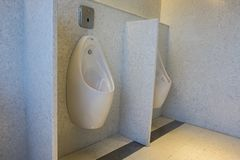 Modern and contemporary interior of public restroom, urinals bow. L in a row Royalty Free Stock Photos
