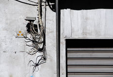 Modern contradictions, mess of different pipes. A crowd of phone and electrical conduits a very messy situation on the facade of a building, landscape cut Royalty Free Stock Photo