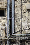 Modern contradictions, mess of pipes. Some gas pipes and a mess of phone conduits on the facade of an ancient building, portrait cut Stock Photos