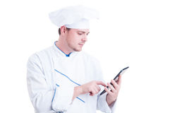 Modern cook or chef using a wireless tablet pc. Browsing internet for recipes concept Royalty Free Stock Photography