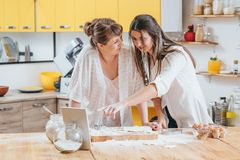 Modern cooking food recipe online video guide. Modern cooking. Food recipe online video guide. Adult daughter using tablet and internet to teach mom new way of stock photos