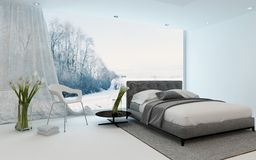 Modern cool bedroom interior overlooking a garden. Modern cool bedroom interior with fresh arums and a double bed overlooking a winter garden through a large Stock Photography