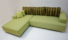 Modern corner sofa. Modern design, green colored sofa with stripe pillows, and decorative, adjustable metal legs Stock Photos