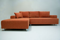 Modern corner sofa. Modernly designed, covered by quality orange textile, including pillows, and decorative, height adjustable metal legs Royalty Free Stock Photo