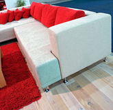 Modern corner sofa. Modern interior consisting white corner sofa with red pillows ans parquet floor with red tufted carpet Stock Photos