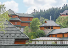 Modern cottages on slope of forested mountains Royalty Free Stock Photo