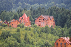Modern cottages on slopes of forested mountains Stock Photography