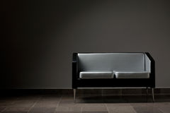 Modern couch. Modern lounge couch against a gray wall. Studio lighting Royalty Free Stock Images