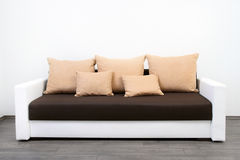 Modern couch. At white wall Royalty Free Stock Photos