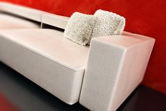 Modern couch 3D rendering. Modern couch with white pillows beside red wall, 3D rendering stock illustration