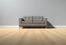 Modern Couch In Room. An empty  room in a house with grey walls and a reflective wooden floor with a modern couch Royalty Free Stock Photo