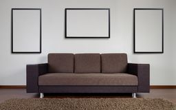 Modern couch with wall decoration frames royalty free stock photography