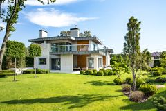 Modern country house with the large lawn and a wooden fence. In front of the house there is a covered terrace with a lounge zone. stock photo