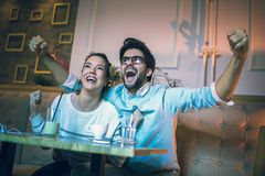 Modern couple in cafe looking football match on tv in cafe. Royalty Free Stock Image