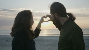 Couple enjoying sunset at the beach and making a heart shape with their hands while looking at the sun and then kissing stock video footage