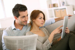 Modern couple looking at news on different supports Royalty Free Stock Photo