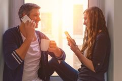 Couple at home. Modern couple on phones while coffeeebreakt royalty free stock images