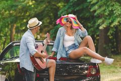 Modern couple taking a break on road trip and enjoying their favorite song. Young fashionable couple playing acoustic guitar on the back side of their royalty free stock images