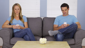 Modern couple using their smartphones on couch Royalty Free Stock Images